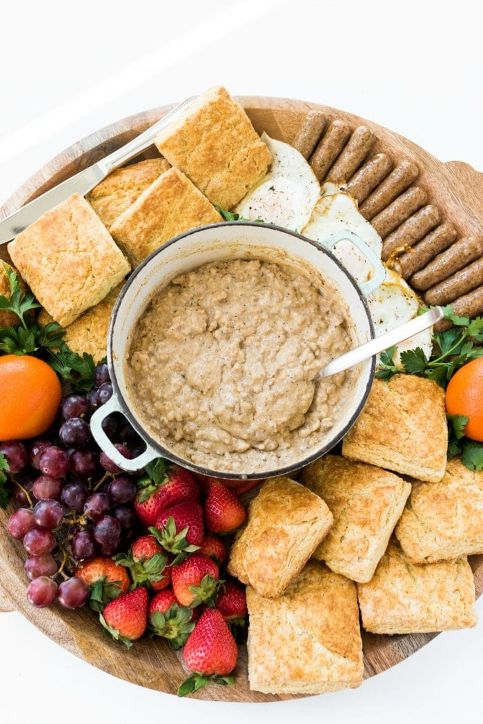 a round food board filled with biscuits and gravy and fresh fruit