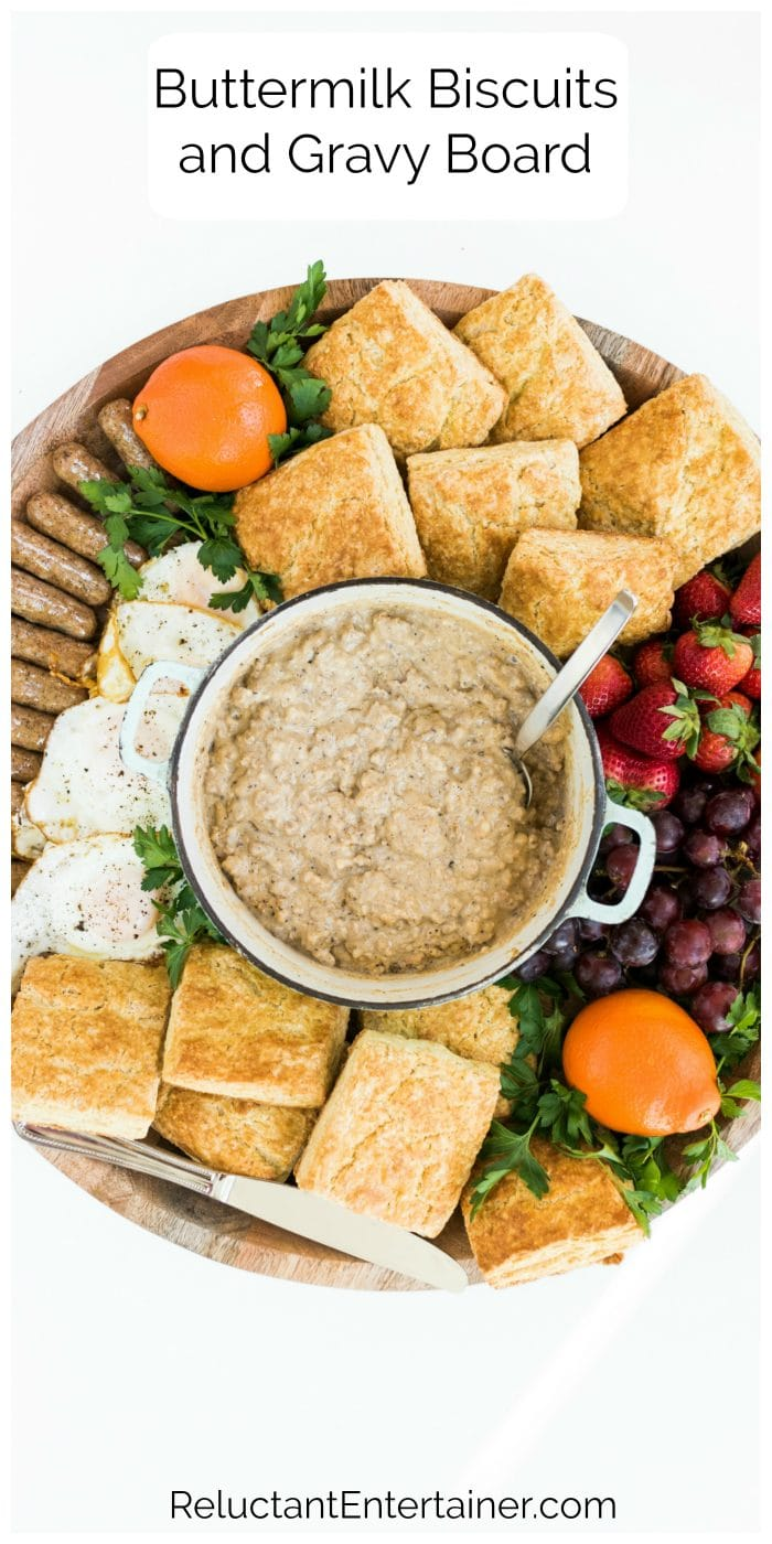 breakfast or brunch board of a pot of pork gravy in the center, surrounded by biscuits and fresh fruit