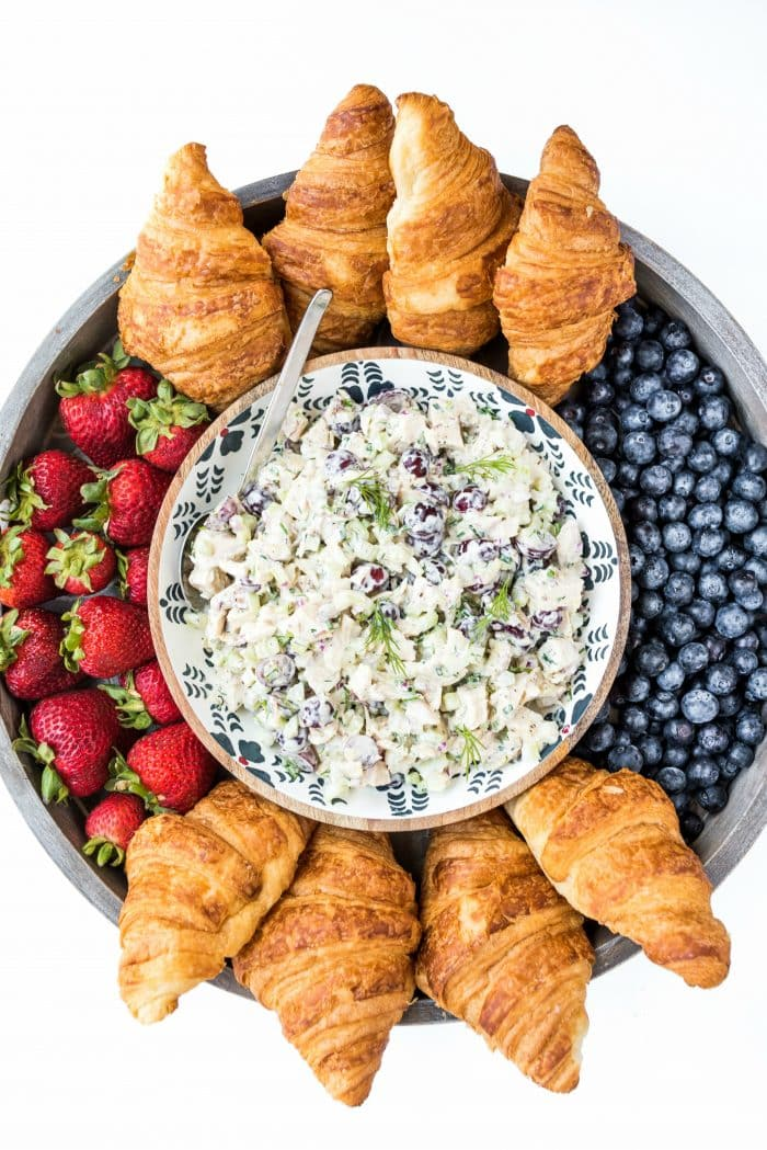 close up shot looking down on a wood board with chicken salad and croissants and fresh berries