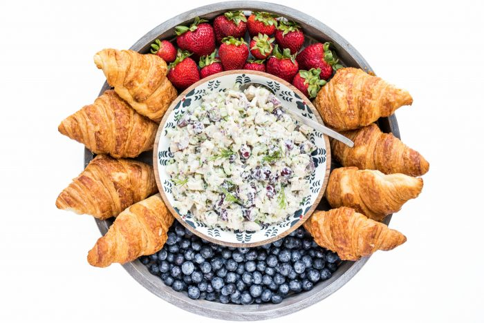 looking down on a wood board with chicken salad sandwich mixture in a separate bowl in the middle, surrounded by croissants, and fresh berries