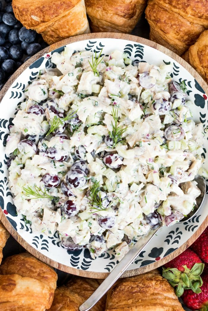 a bowl of chicken salad with purple grapes