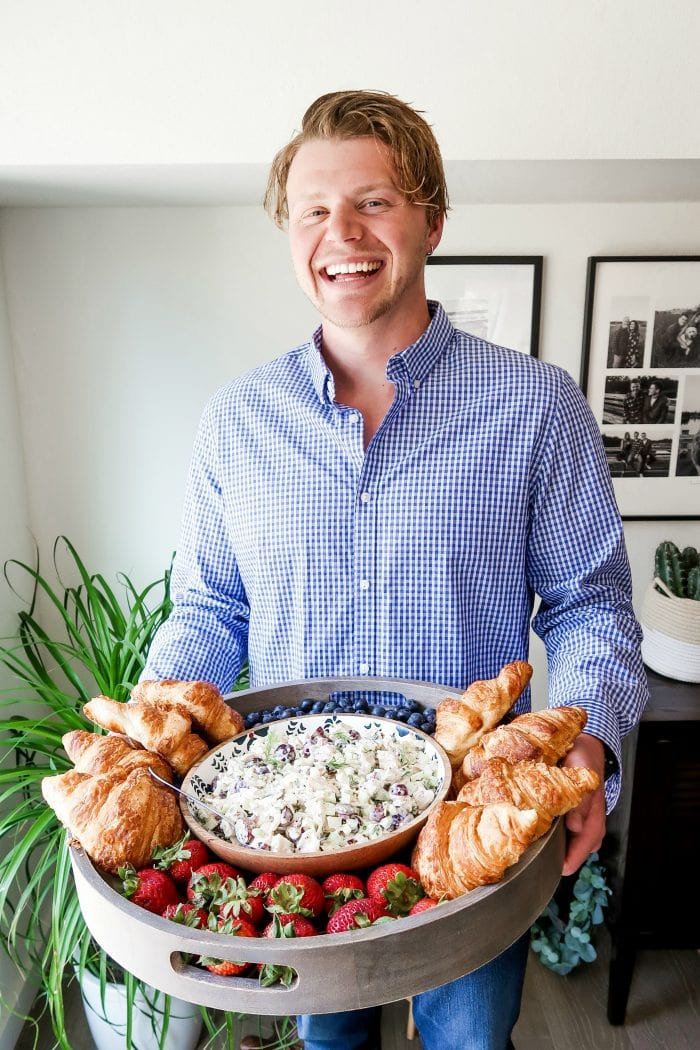 man laughing holding a large wood board filled with chicken salad, croissants, and berries