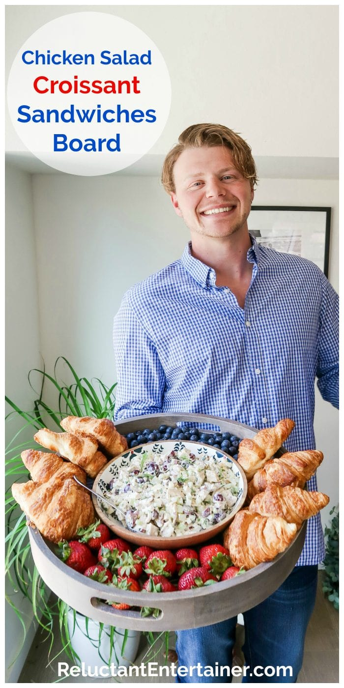 man holding a large wood board filled with chicken salad, croissants, and fresh berries