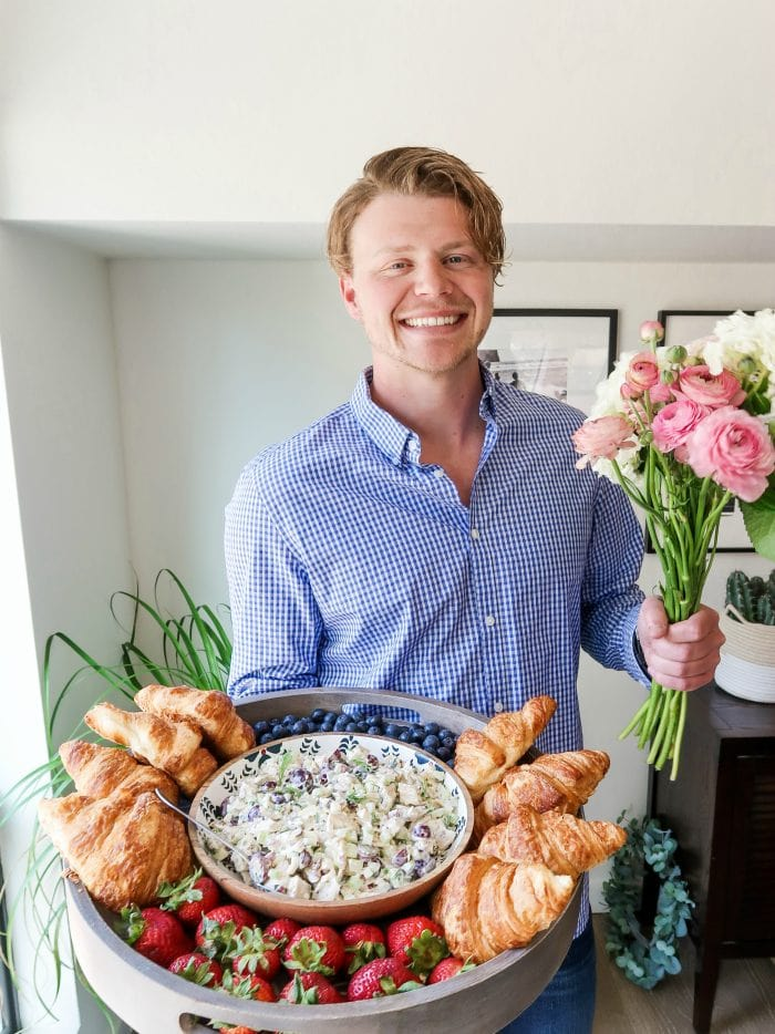 man holding a large wood board filled with chicken salad, croissants, and fresh blueberries and strawberries and fresh flowers