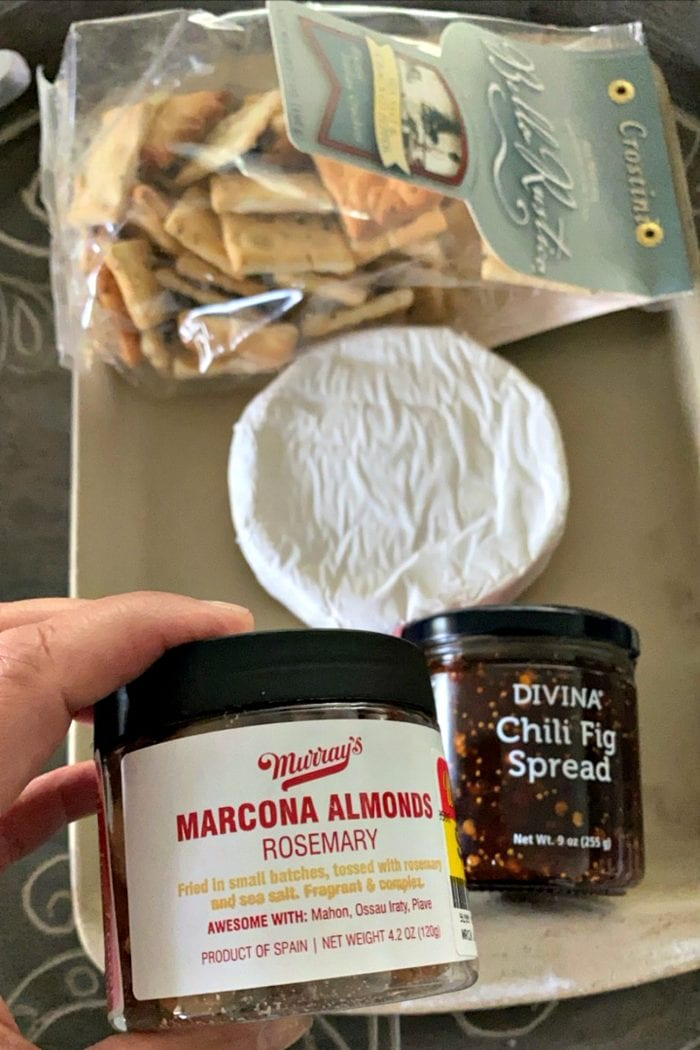 jar of chili fig spread and marcona almonds, with a round of uncooked brie cheese