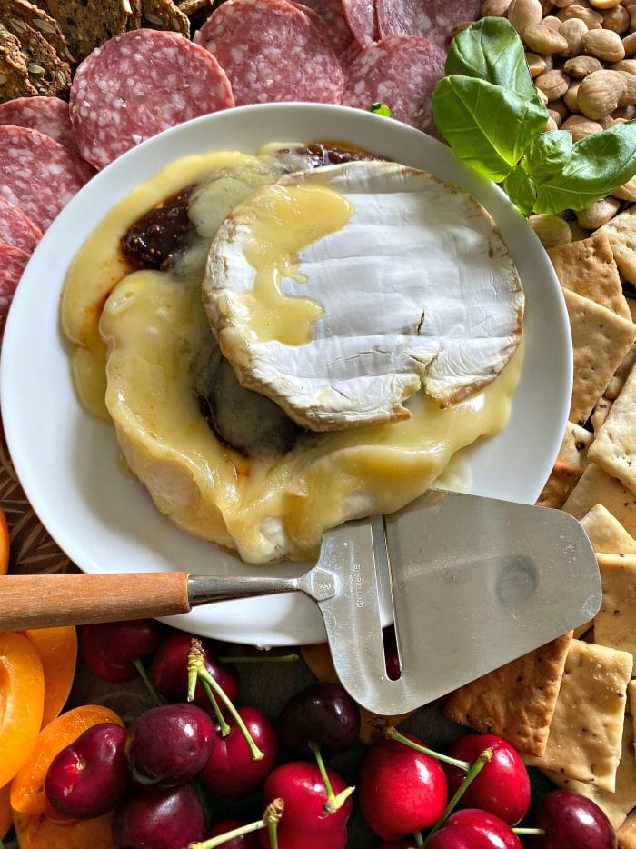 a round of melted brie cheese with chili fig