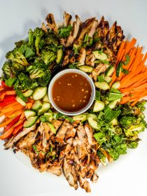 a platter of chicken thighs cut into strips with veggies, and dip in a bowl in the center