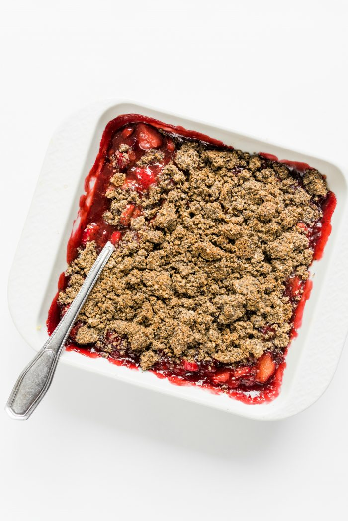 white square baking dish with poppyseed crisp topping over strawberries and rhubarb