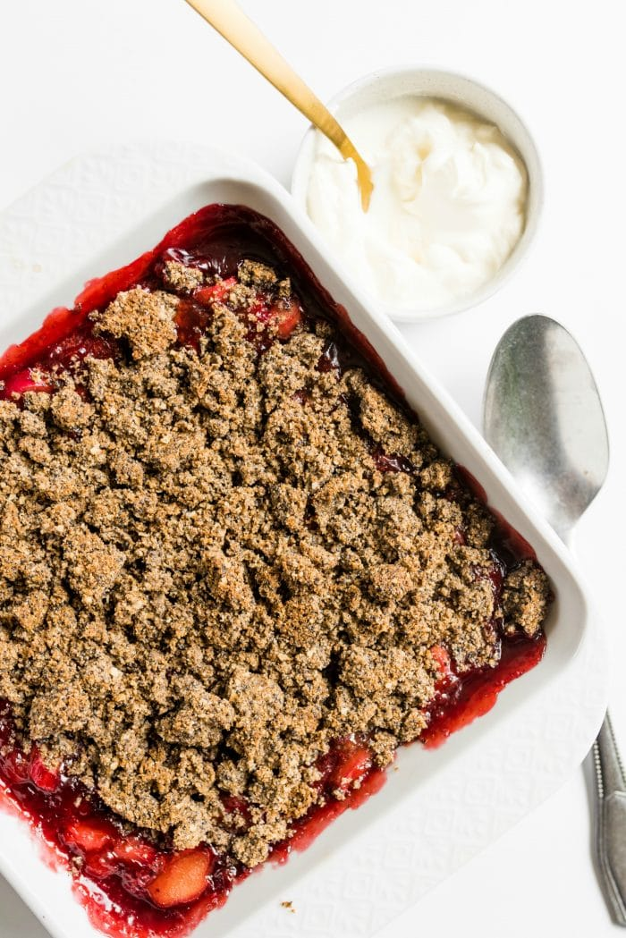 whipped cream in a small bowl with strawberry rhubarb crisp in white baking dish