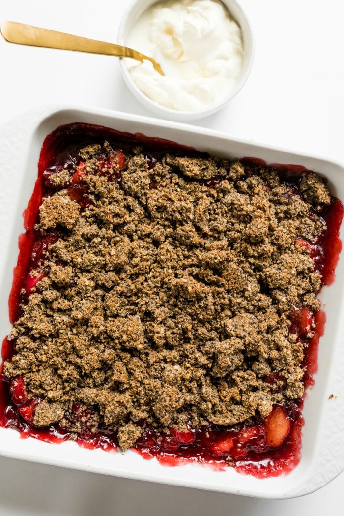 square pan of strawberry rhubarb crisp with a small bowl of whipped cream