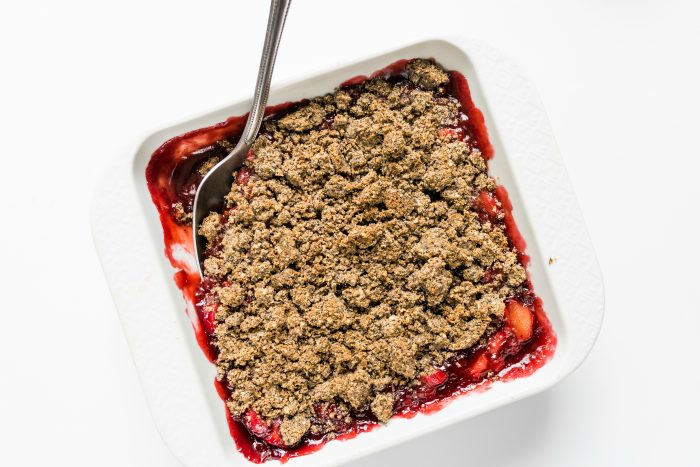 white square baking dish of strawberry rhubarb crisp