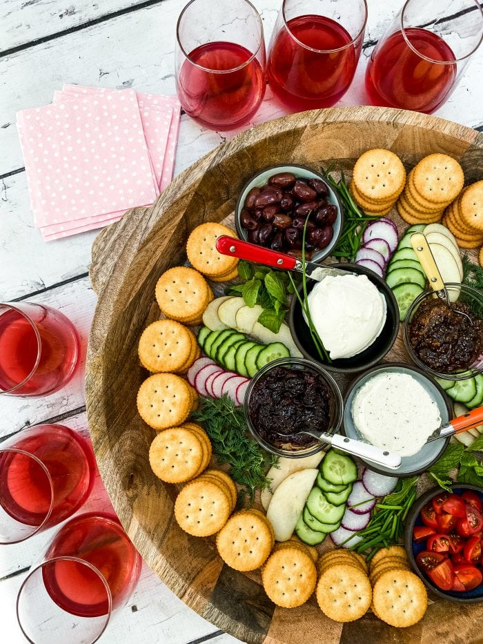 round tray of crackers and cheese snacks with red drinks