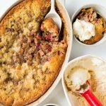lookng down on a rhubarb strawberry cobbler with a side serving, and scoop of vanilla ice cream