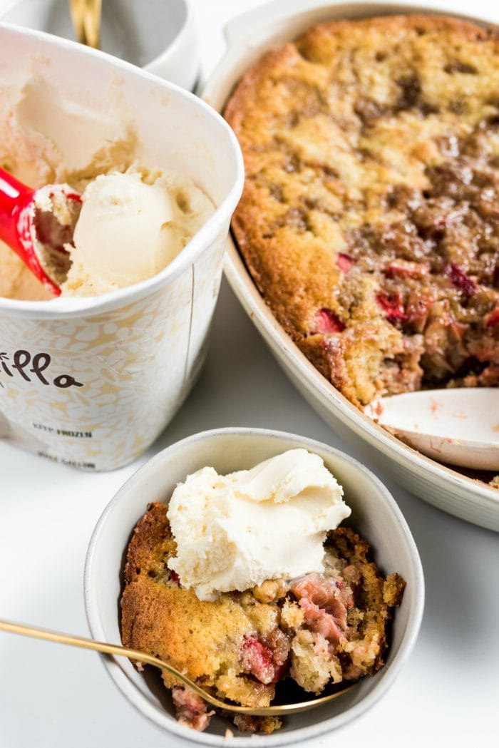 close up of rhubarb strawberry cobbler scooped into a small bowl, with vanilla ice cream