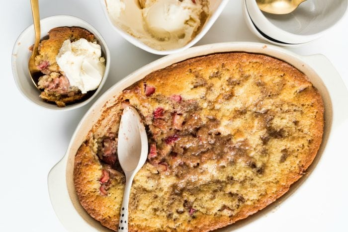 a baked rhubarb strawberry cobbler with a spoonful in a small bowl with ice cream
