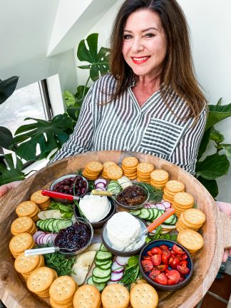 woman holding a round tray of stacked crackers, soft cheese, veggies, and herbs