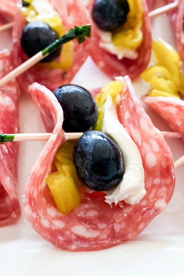 close up of one salami slice with cream cheese spread on top, with 2 blueberries, a piece of pepperoncini, folded together with a toothpick