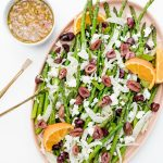 Shaved Fennel Asparagus Salad on an oblong platter wth a small bowl of orange dressing and gold serving tongs