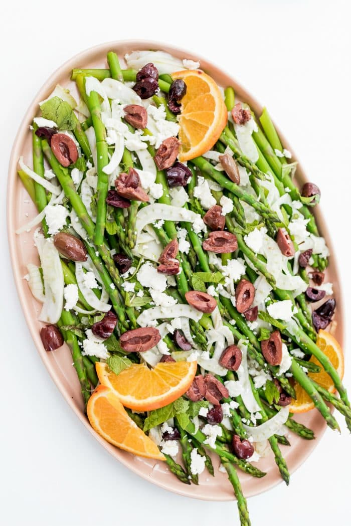 a soft pink plate filled with a Shaved Fennel Asparagus Salad