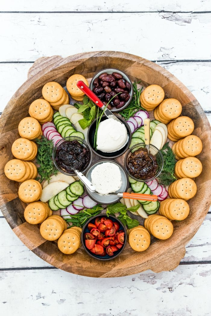 round platter of soft cheese, veggies, and jam with Ritz crackers