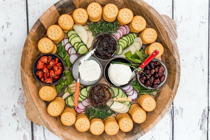 round tray of crackers, cheese, veggies, and jam