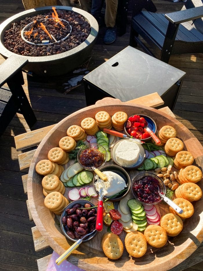 round tray of Ritz crackers with veggies and cheese by an outdoor fire