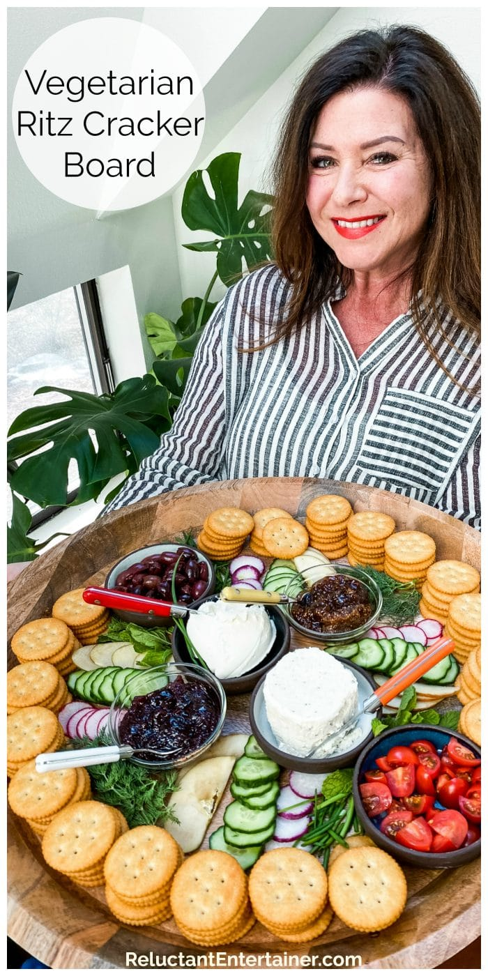 lady in black and white striped blouse holding a large round tray of Ritz crackers, cheese, veggies, jams