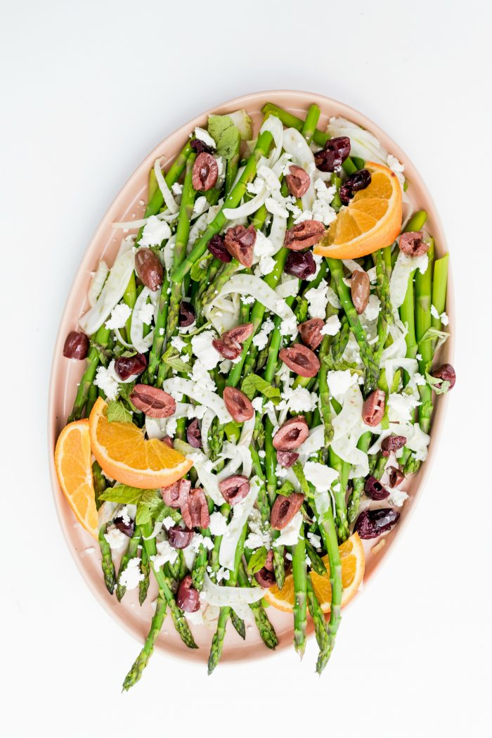 pink oblong plate with asparagus and fennel salad, garnished with orange slices