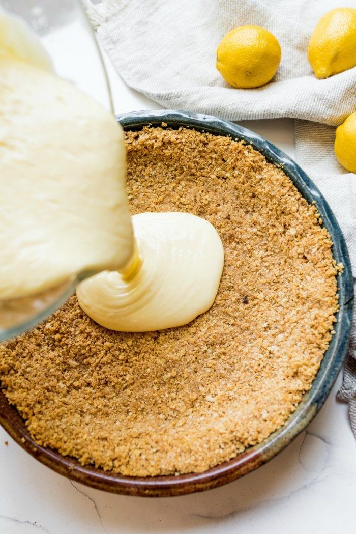 pouring lemon pie filling into a Ritz cracker crust