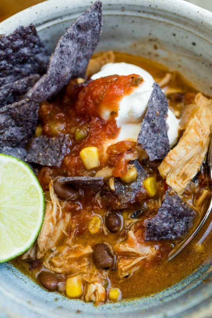 close up small bowl of chicken tortilla soup with sour cream, chips, and salsa