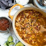 oval pot of chicken tortilla soup with black beans, corn, served with salsa, sour cream, lime, tortilla chips