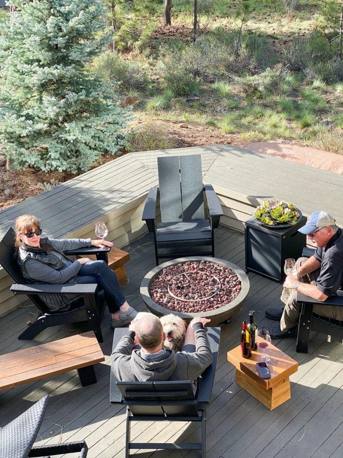 sitting on a deck wtih a few friends around a fire pit