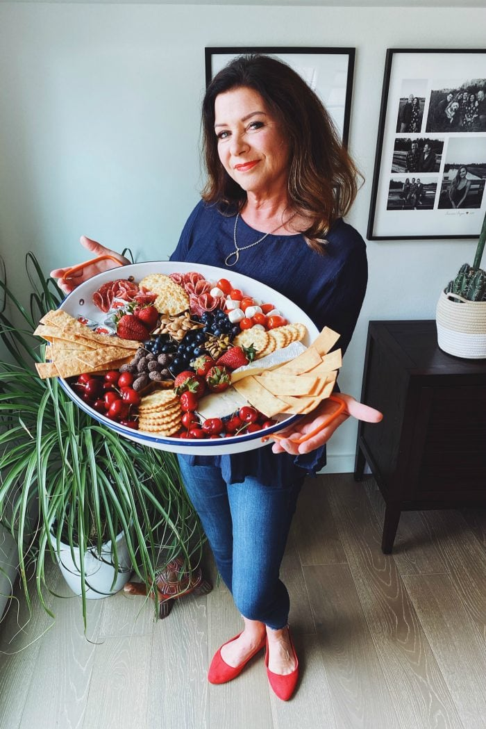 woman holding an oval tray with cheese and crackers and fruit for the 4th of July