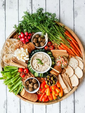 large round platter with vibrant veggies cut up, cashew dip, vegan meatballs, and more