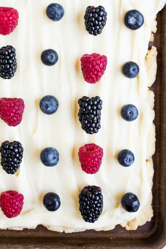 close up of sugar cookie bars in a pan, with fresh blueberries, blackberries, raspberries, and white frosting