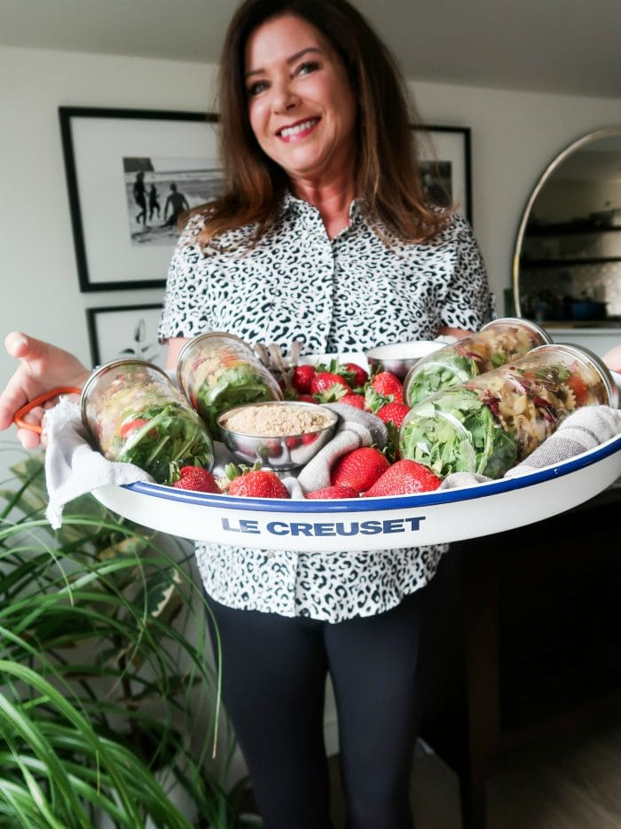 woman holding a tray with 4 canning jars filled with bowtie pasta salad
