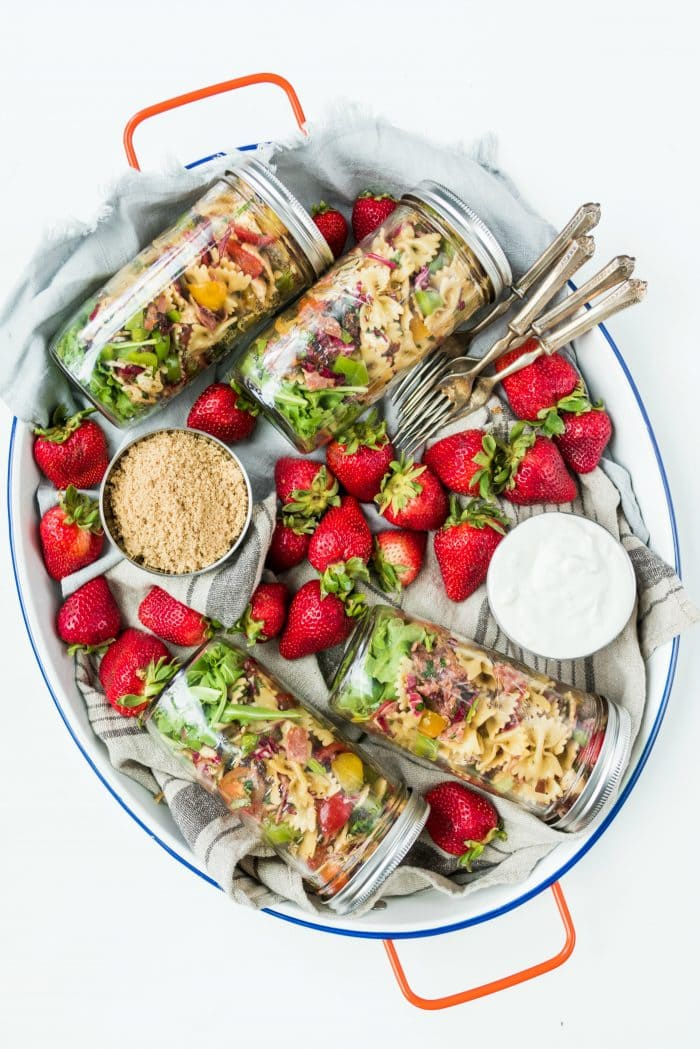 oval tray with 6 filled jars of pasta salad, with strawberries