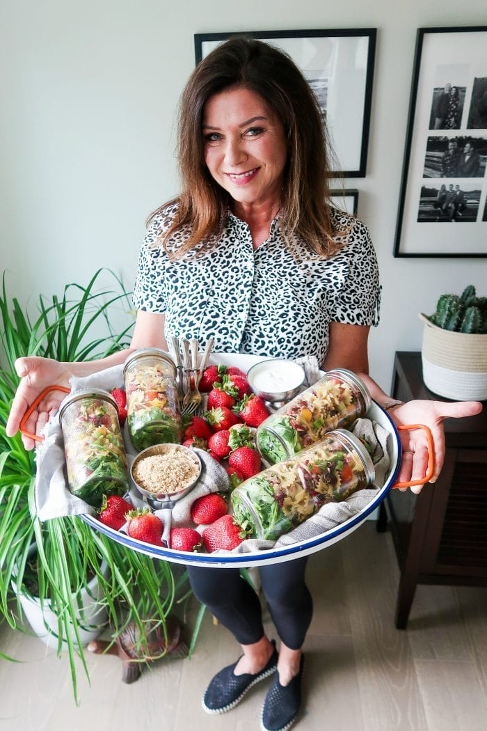 woman holding a tray with 4 canning jars filled with pasta salad
