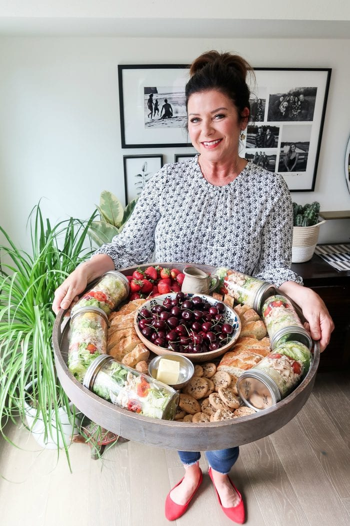 a woman holding an epic board filled with food (salad, cherries, strawberries, bread)