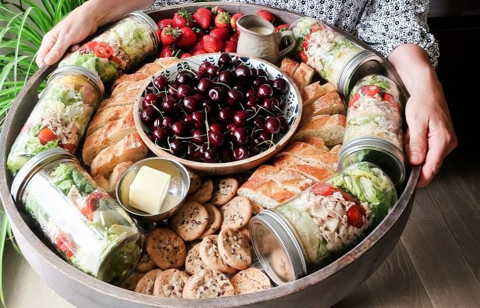 a big board of food with cherries in the middle, with jars of salad, bread, and cookie