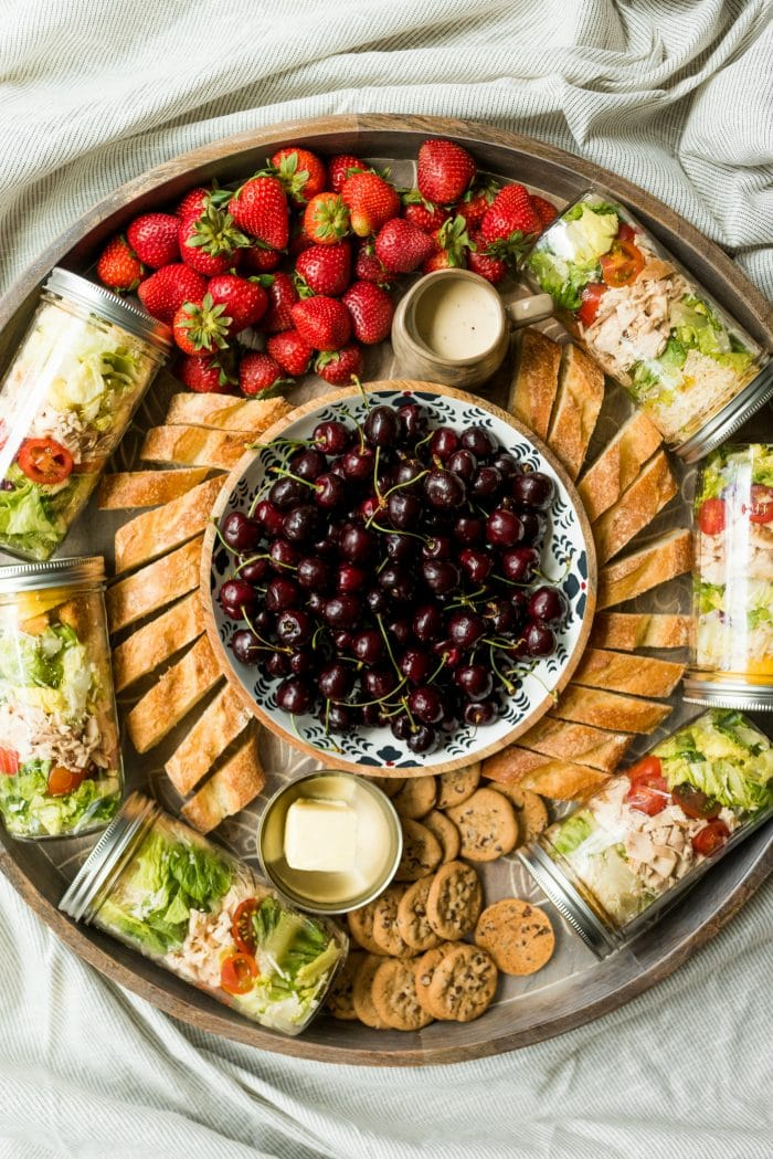 a round board with jars of salad, bread, strawberries, and a bowl of cherries