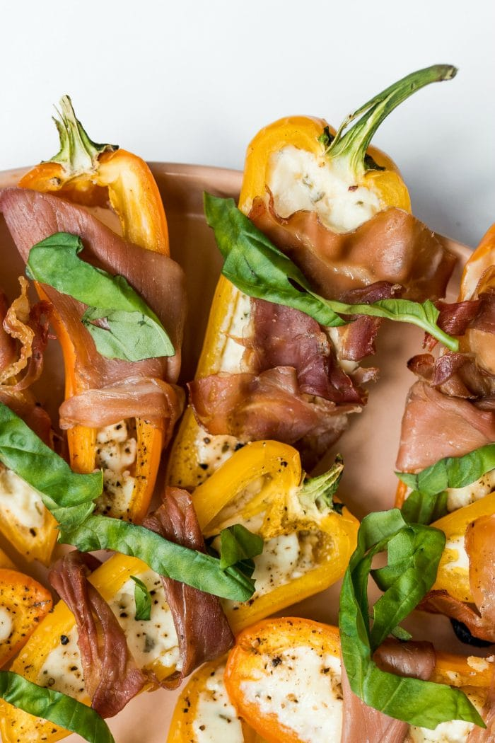 close up of Prosciutto-Wrapped Mini Peppers garnished with fresh basil
