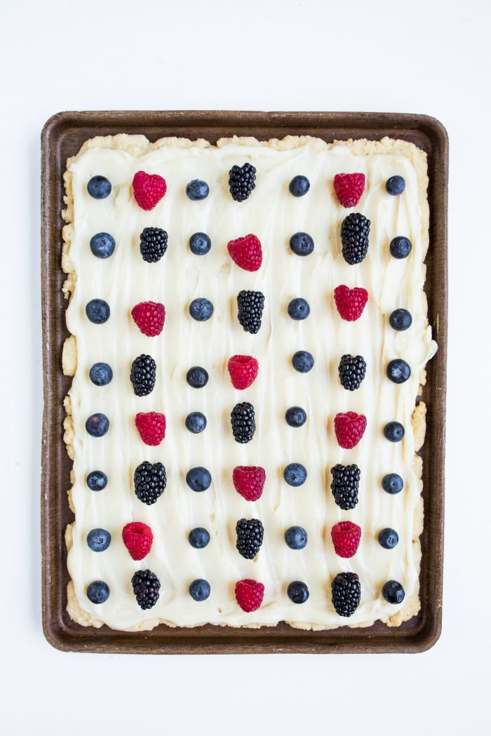 a baking pan of easy sugar cookie bars (crust) with white cream cheese frosting and fresh summer berries