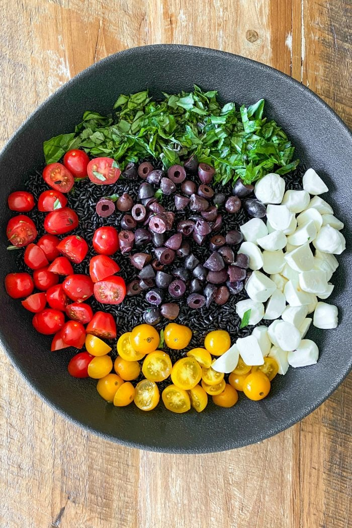 black bowl of black rice salad ingredients: forbidden rice, mozzarella cheese balls, cherry tomatoes, olives, and basil