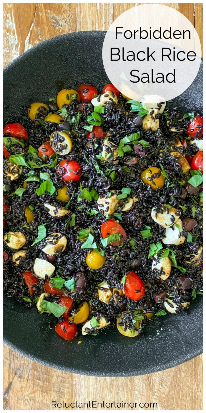 close up black rice salad with tomatoes, basil, cheese