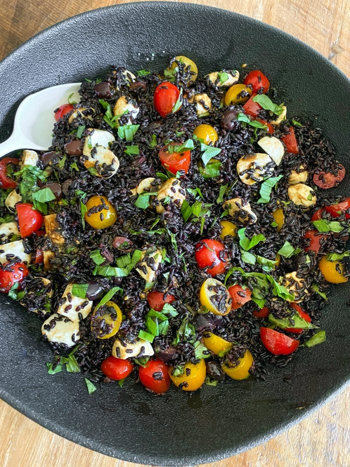 black bowl of black rice salad with colorful tomatoes, cheese, and basil