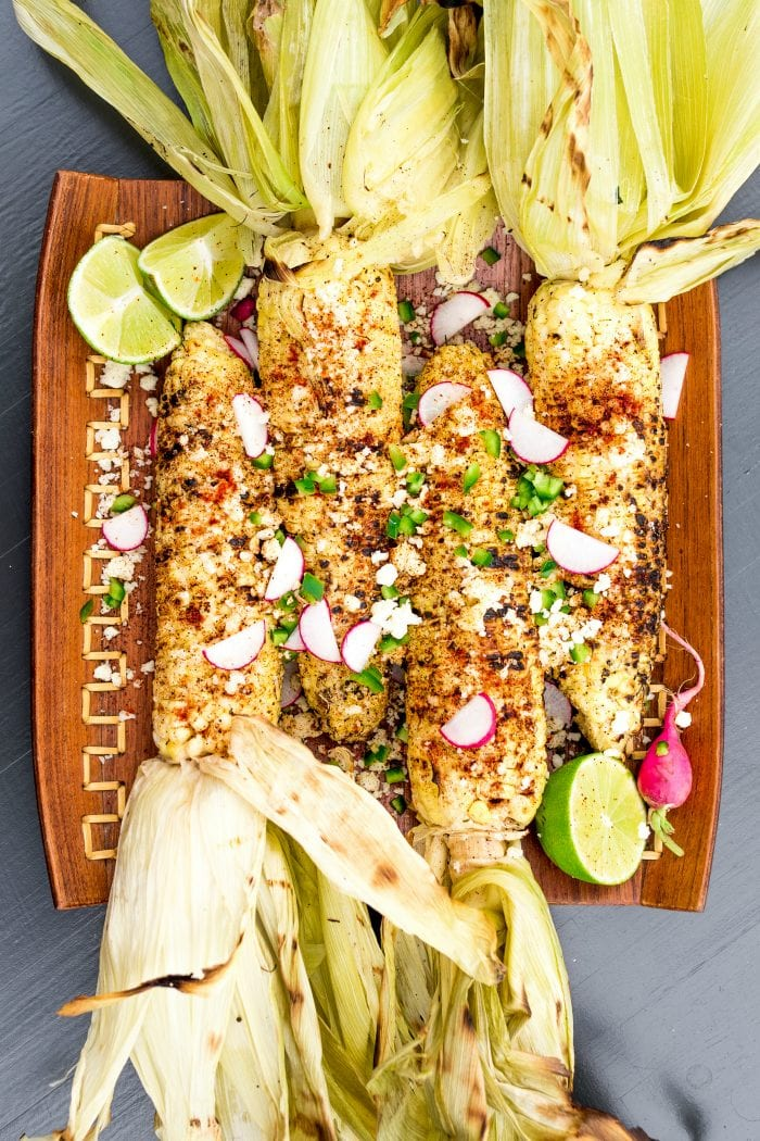 plate of charred grilled corn on the cob (with husks)