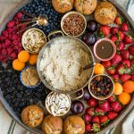 looking down on a round tray with an oatmeal breakfast (pot of oatmeal and toppings)