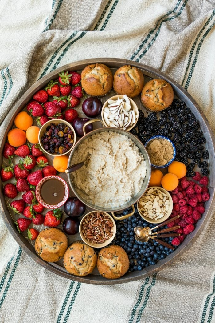 an epic wood board with a pot of oatmeal, toppings, and fresh fruit