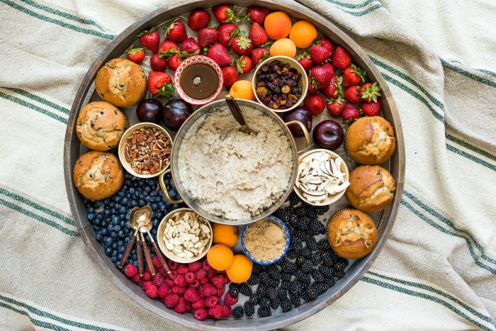 a beautiful round board with pot of oatmeal, small bowls with toppings, fresh fruit, and blueberry muffins